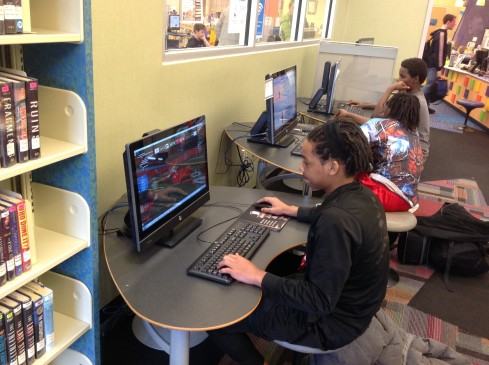 Three teens playing video games on separate desktop computers.