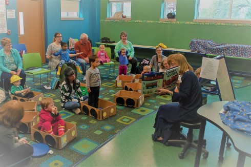 Storytime at Glen Allen Library. Librarian is reading Chugga Chugga Choo Choo to an attentive crowd of young children and caregivers.