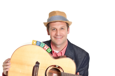 """Portrait of Chris Campbell holding an acoustic guitar with """"Chris"""" spelled out in block letters balanced on the guitar."""