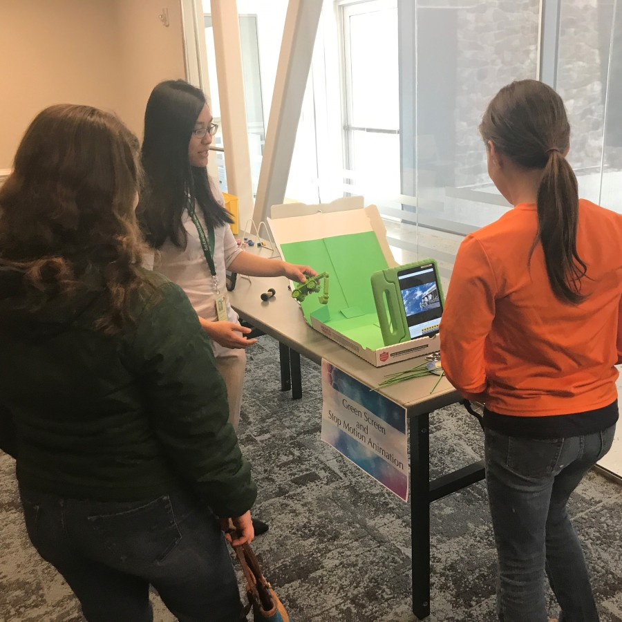 Two women listening to a third woman explain stop motion animation with a green screen.