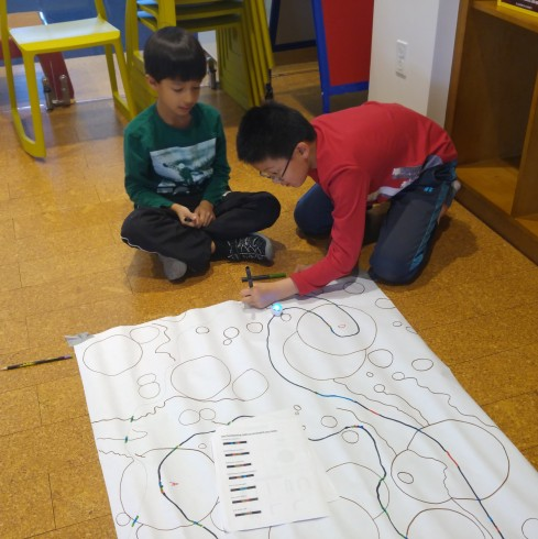 two young children sitting on the floor creating a maze for the Ozobot robots to explore.