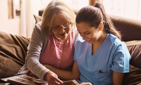 Shot of a nurse and a senior woman looking at a photo album together.