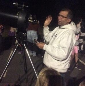 Astronomer explaining how to use telescope.